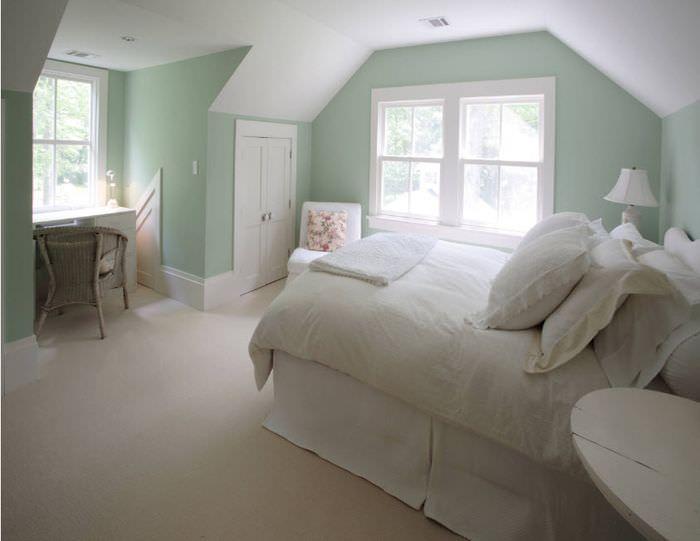 Белая кровать и мятные стены в спальне частного дома