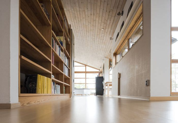 Книжные стеллажи из натурального дерева в коридоре частного дома