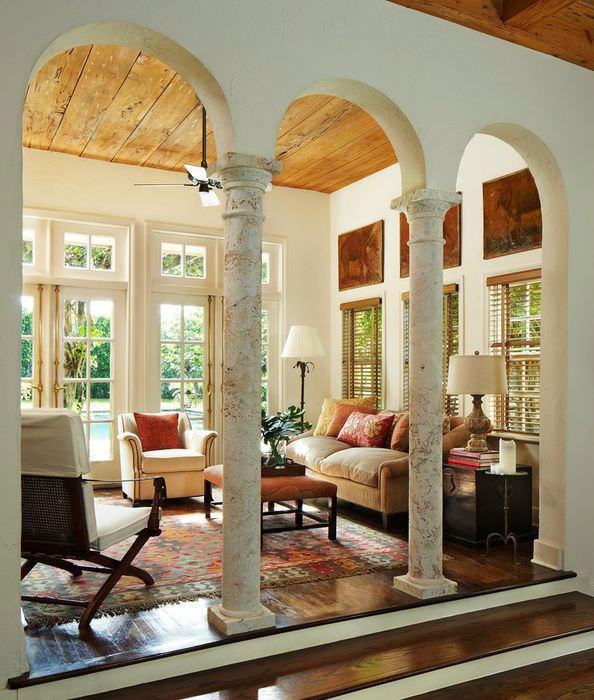 Дизайн гостиной частного дома с колоннами из натурального камня