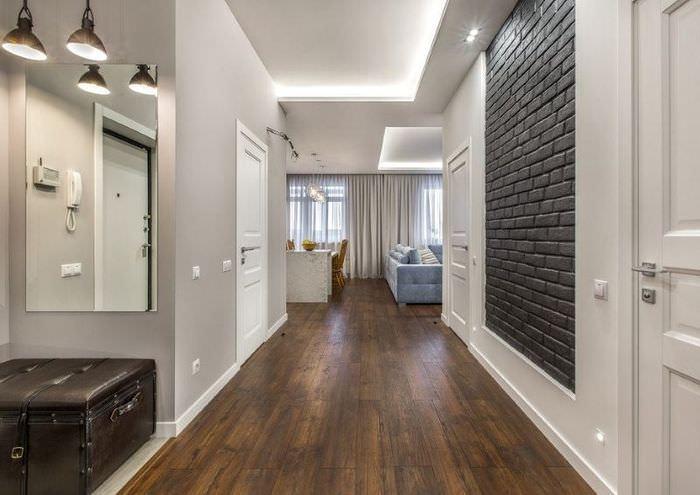 Кирпичная стена темно-серого цвета в интерьере узкого коридора с белыми дверями