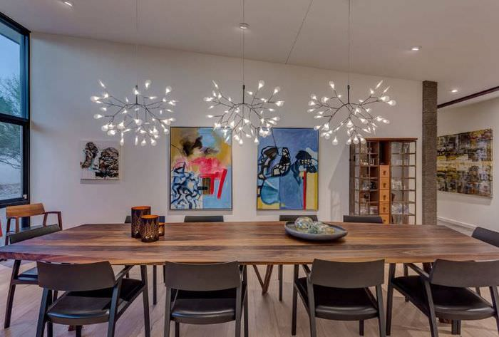 Интерьер гостиной загородного дома с тремя люстрами над деревянным столом