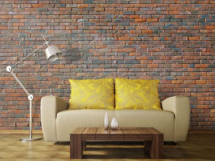 Диван с обивкой кремового окраса перед кирпичной стеной