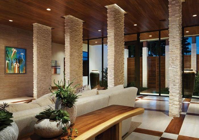Зонирование пространства гостиной с помощью колонн из натурального камня