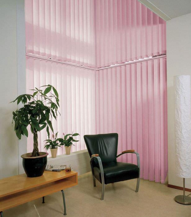 Черное кресло на фоне светло-розовых жалюзи