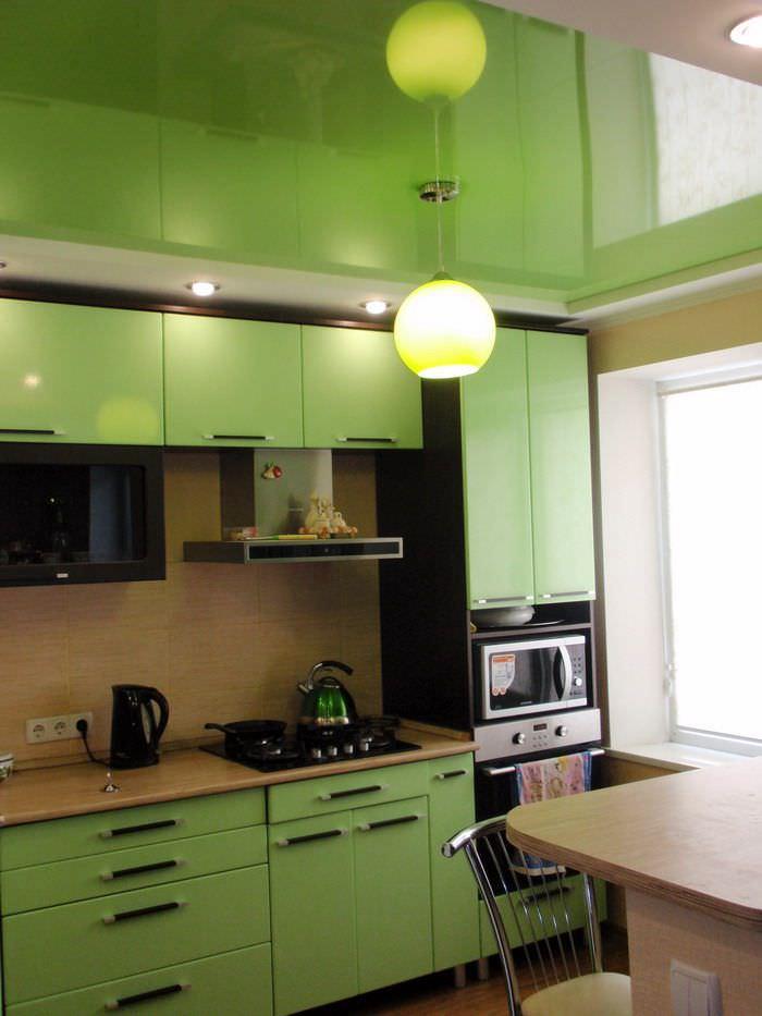 Зеркальный натяжной потолок на кухне с зеленым гарнитуром