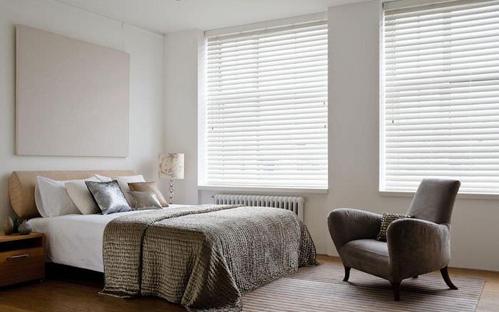 Белые горизонтальные жалюзи в спальне с серым покрывалом