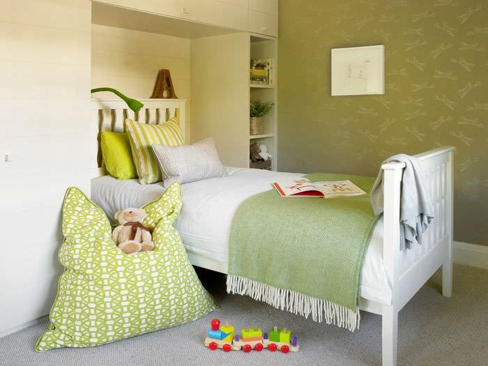 Подушка с орнаментом зеленого оттенка около детской кровати