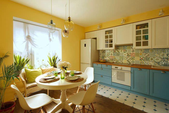 Бело-голубой гарнитур в кухне с желтыми стенами