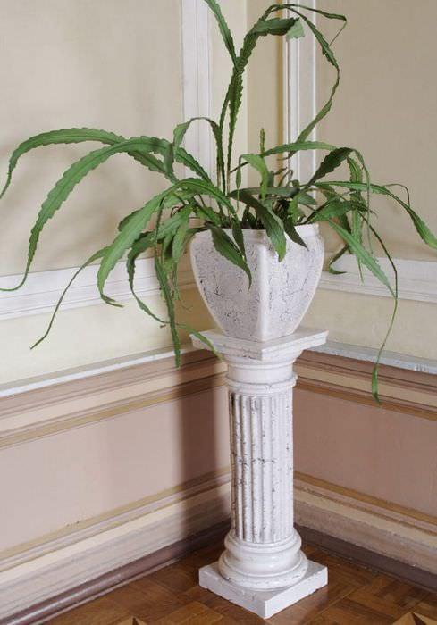 Ваза с растением на пьедестале из камня