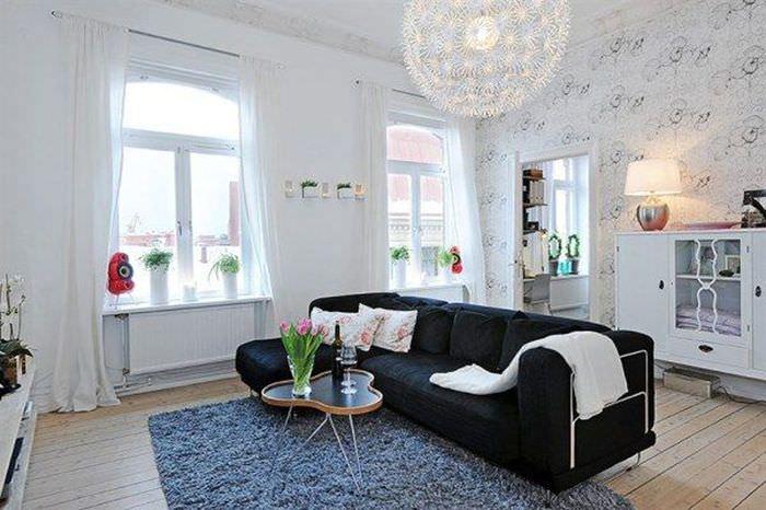 Черный диван посередине просторной гостиной с двумя окнами