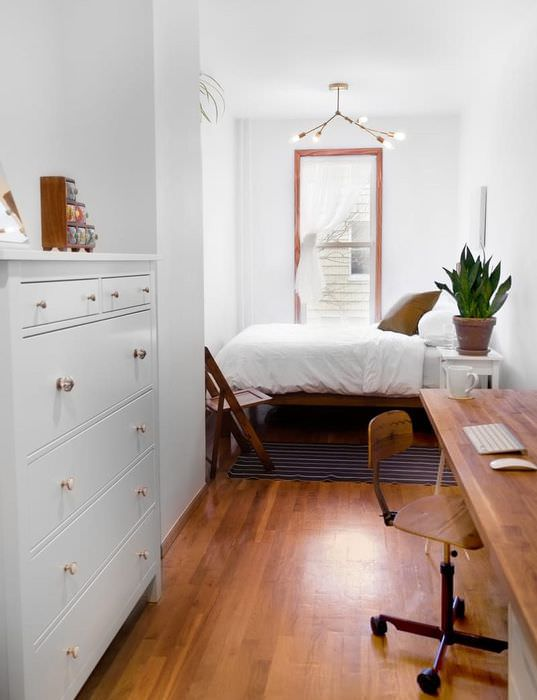 Коричневый стол в спальне с белыми стенами