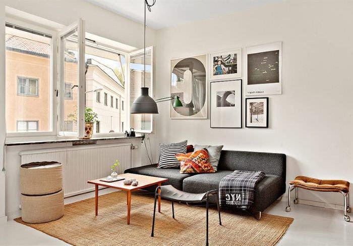 Интерьер светлой гостиной с черным диваном