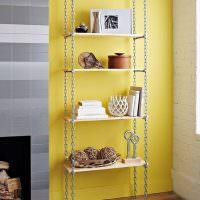 Полки на цепях на фоне желтой стены