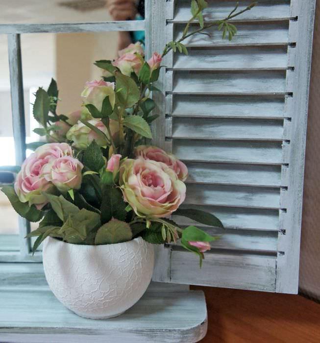 Горшок с цветущими розами на деревянном подоконнике