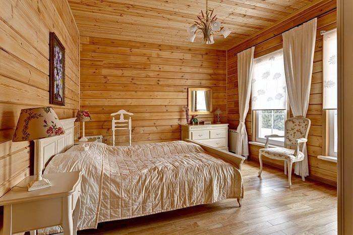 Белая кровать в спальне дома из клееного бруса