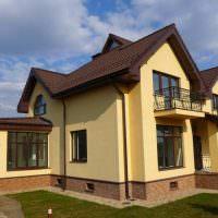 Желтые оштукатуренные стены дачного дома