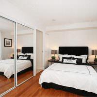 Зеркальная стена в спальне с белой кроватью