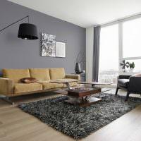 Серая стена в гостиной с минимумом мебели
