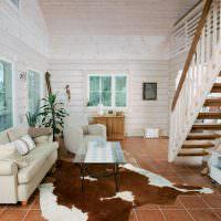 Гостиная загородного дома с деревянной лестницей