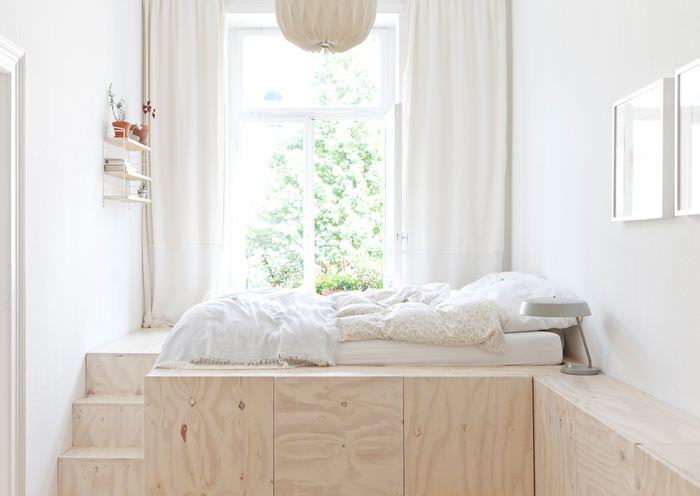 Белая кровать на подиуме из фанеры