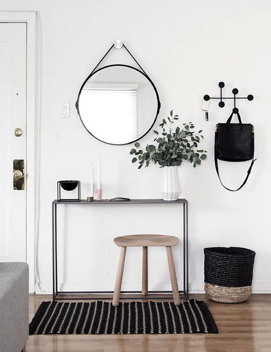 Круглое зеркало в черной оправе на белой стене прихожей