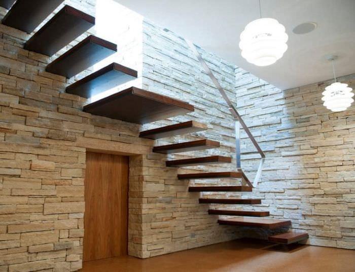 Лестница на больцах на стене с отделкой из природного камня