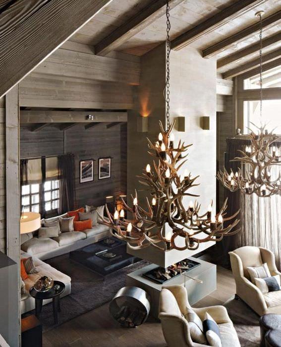 Огромные люстры из рогов оленей на потолке гостиной в деревянном доме