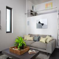 Серый диван в комнате с узким окном
