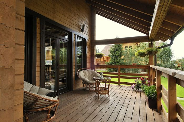 Два кресла из ротанга на открытой террасе загородного дома