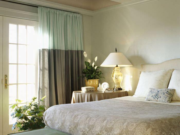 Двухцветные шторы в спальне с лампой на тумбочке