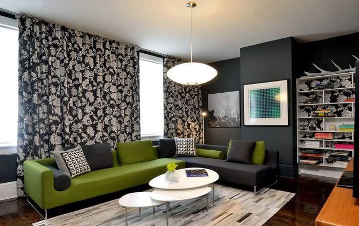 Зеленый диван в комнате с темными стенами