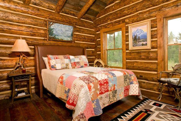 Пестрое покрывало из лоскутов ткани на кровати в бревенчатом доме