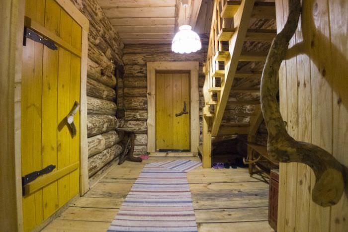 Интерьер прихожей с лестницей в срубовом доме