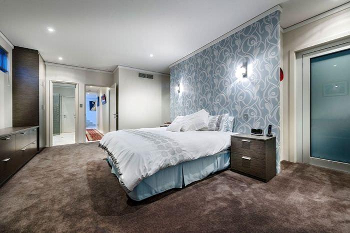Пятнистый пол спальни с бумажными обоями на стене