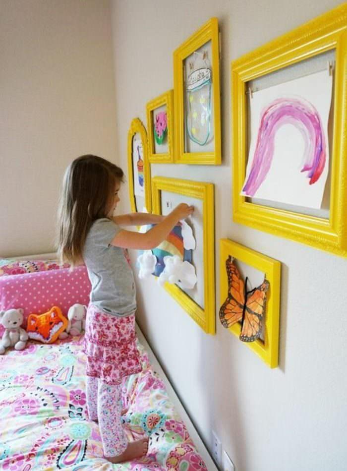 Девочка украшает комнату собственными рисунками