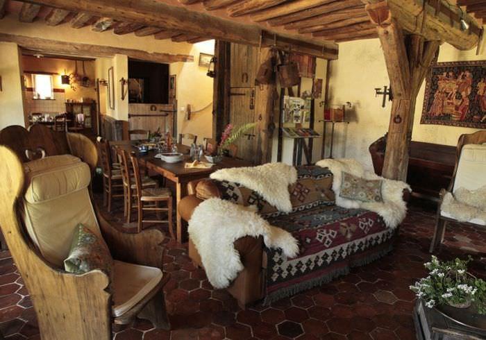 Белые шкуры животных на диване в гостиной деревянного дома