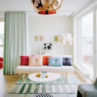 Яркие декоративные подушки на диване гостиной
