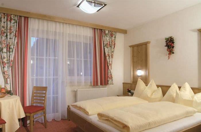Укороченные шторы над батареей отопления в спальне
