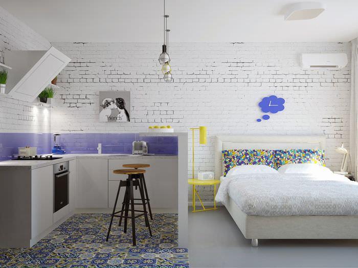 Белая кирпичная стена в маленькой квартире стиля лофт