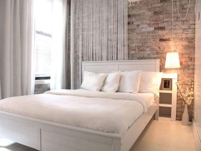 Белая кровать в спальне с кирпичной стеной