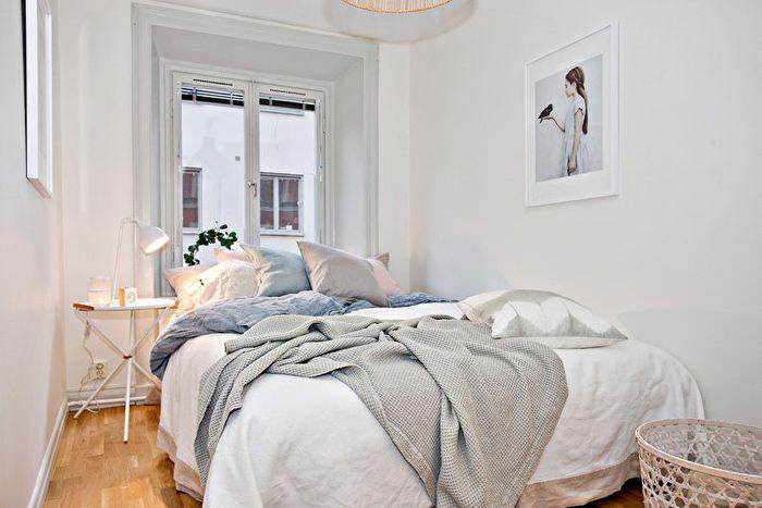 Белая двухспальная кровать в интерьере узкой спальной комнаты
