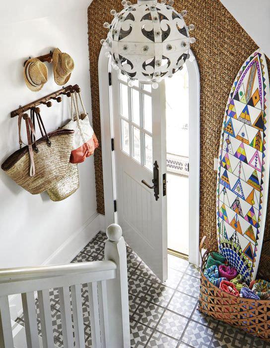 Белая входная дверь в коридоре с лестницей