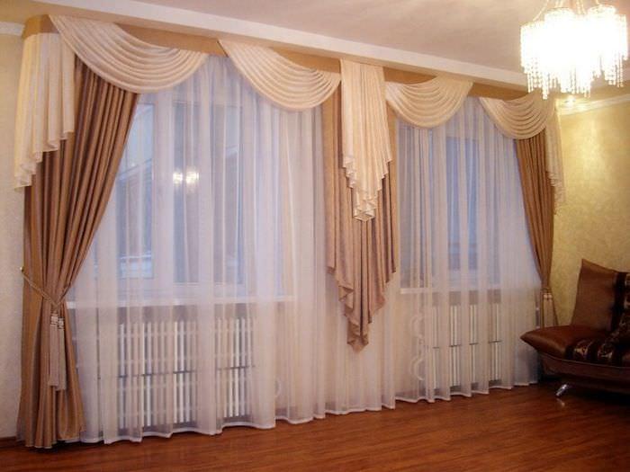 Оформление шторами гостиной с двумя окнами