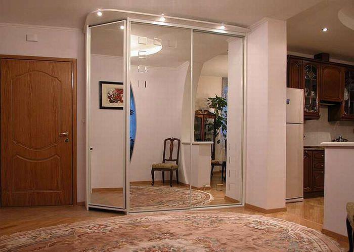 Отражение интерьера прихожей в зеркальных дверцах шкафа-купе
