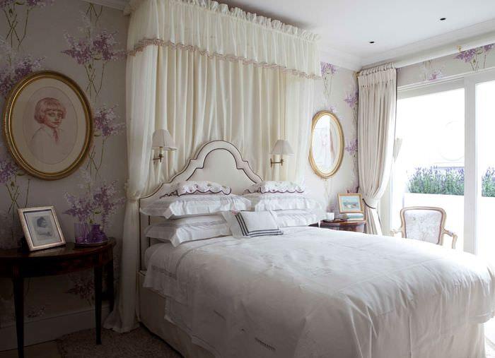 Белый балдахин в спальне с портретами на стене