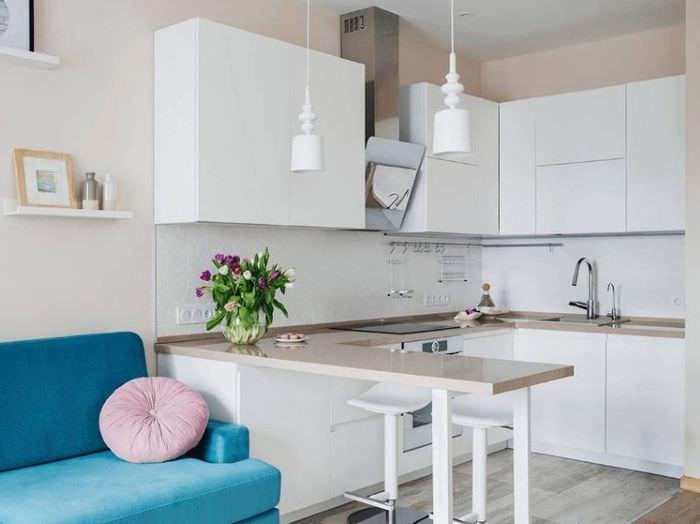 Белая кухня с барной стойкой и бирюзовым диваном