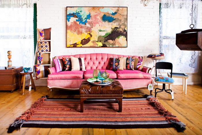 Розовый диван в комнате дачного дома в стиле бохо