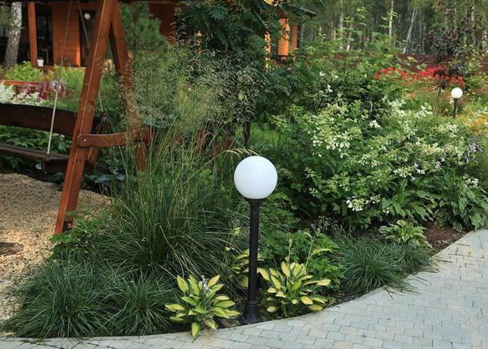 Небольшой садовый фонарик на клумбе с хостами