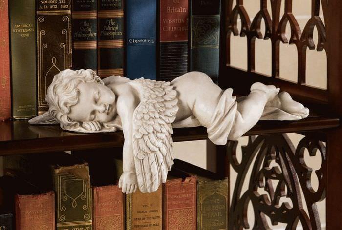 Фигурка ангела на полке с книгами