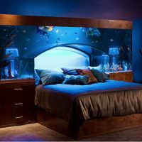 Большой аквариум над кроватью в спальной комнате